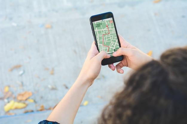 Vrouw die gps kaartnavigatie app met geplande route gebruikt