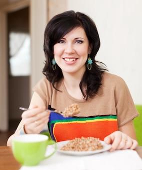 Vrouw die graangewas thuis eet