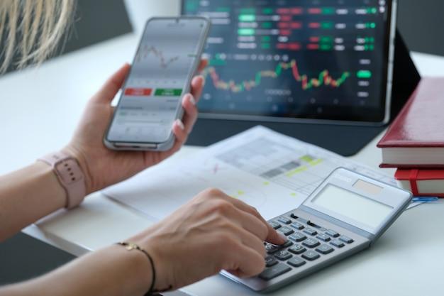 Vrouw die grafiek op het scherm van de mobiele telefoon bekijkt en op rekenmachineclose-up winstgevend rekent