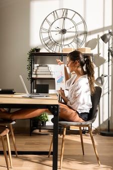 Vrouw die grafiek toont aan laptop