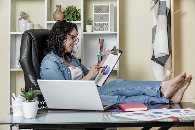 Vrouw die grafieken in huisbureau analyseren