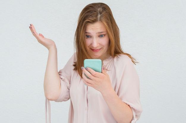 Vrouw die grappig haar mobiele telefoon bekijkt
