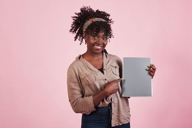Vrouw die grijze blocnote in haar handen houdt bij roze studioachtergrond