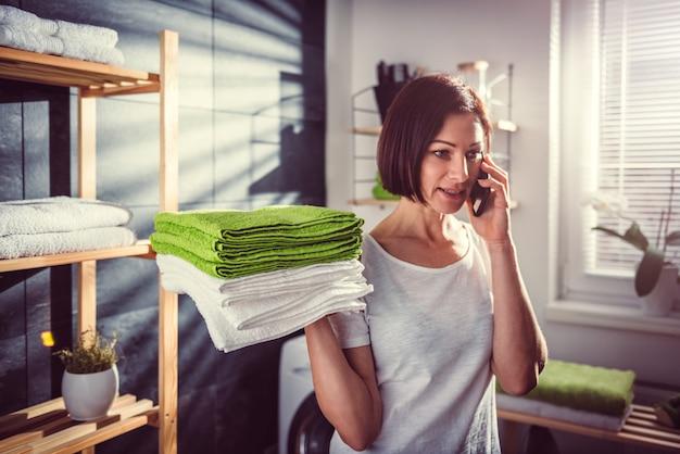 Vrouw die groene gevouwen handdoeken houdt en op telefoon spreekt
