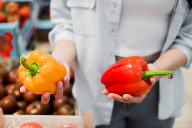 Vrouw die groene paprika in kruidenierswinkelopslag kiest