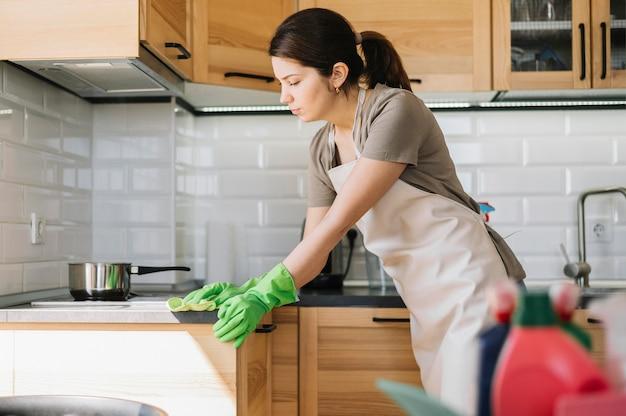 Vrouw die groene rubberhandschoenen draagt