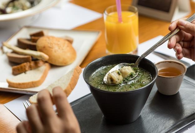 Vrouw die groene soep met saus op een zwarte kom eet