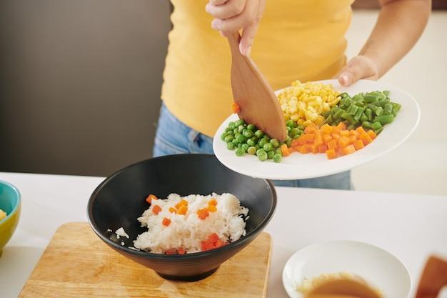 Vrouw die groente aan rijst toevoegt