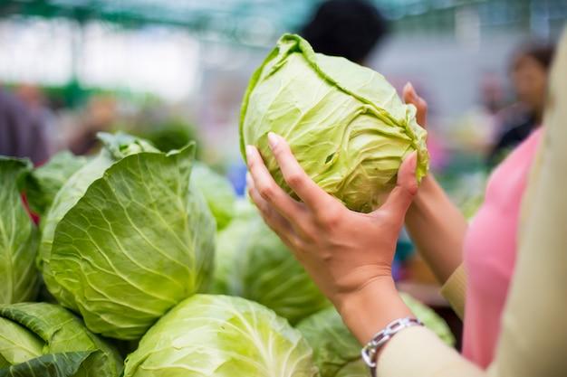 Vrouw die groenten op de markt koopt