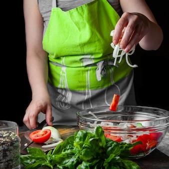 Vrouw die groenten toevoegen in salade zijaanzicht.