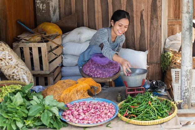 Vrouw die groenten verkoopt, glimlacht terwijl ze met een zak gevuld met sjalotten in een groentestal zit