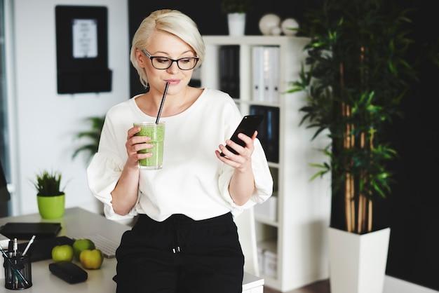 Vrouw die groentesap drinkt en mobiele telefoon gebruikt