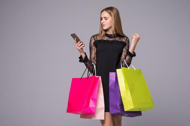 Vrouw die grote het winkelen zakken voor grijze achtergrond houdt