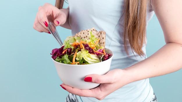 Vrouw die grote kom met plantaardige salade houdt