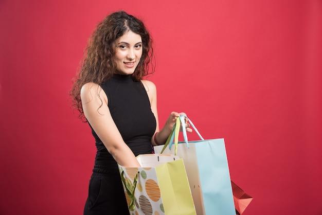 Vrouw die haar aankopen op rode achtergrond toont. hoge kwaliteit foto