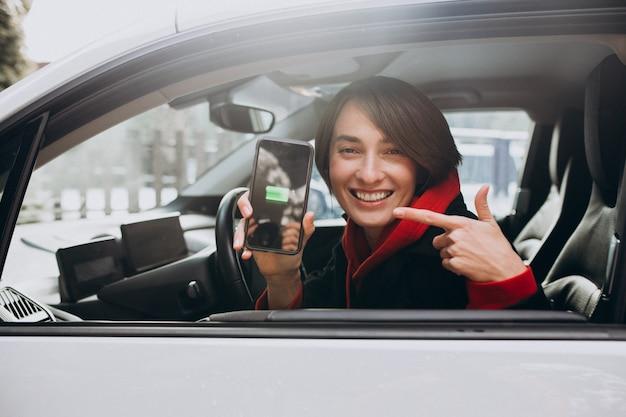 Vrouw die haar auto laadt en de cherger op bhertelefoon bekijkt