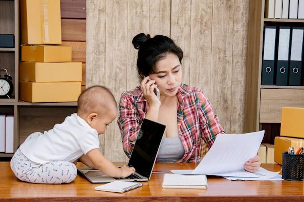 Vrouw die haar baby behandelt terwijl het werken op het kantoor