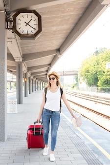 Vrouw die haar bagage helemaal over het station loopt