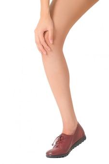 Vrouw die haar been met het masseren van knie op pijngebieden houden die op witte achtergrond wordt geïsoleerd