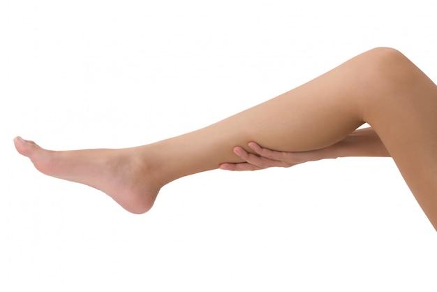 Vrouw die haar been met masserend die kalf op pijngebied houden op wit wordt geïsoleerd
