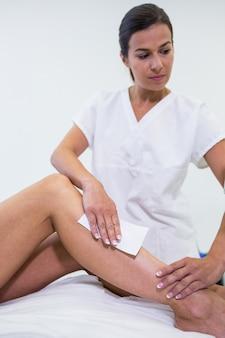 Vrouw die haar beenhaar verwijdert