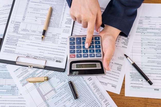 Vrouw die haar belastingen berekent, 1040 individueel belastingformulier
