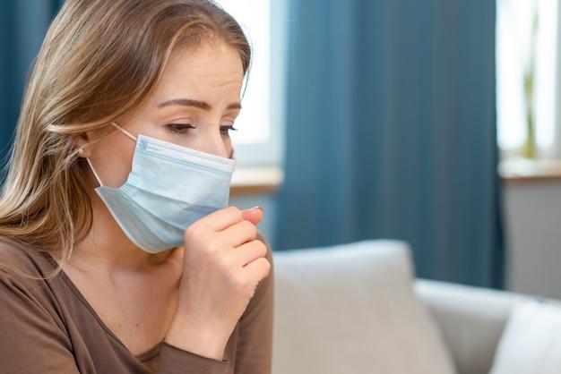 Vrouw die haar beschermend masker gebruikt terwijl het hoesten