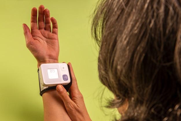 Vrouw die haar bloeddruk meet.