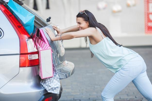 Vrouw die haar detailhandel in de auto probeert in te pakken. niet genoeg ruimte voor de aankoop. winkelend meisje. shopaholic bij het winkelen.
