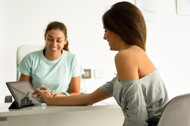 Vrouw die haar diagnose met vrouwelijke fysiotherapeut goedkeurt en ondertekent.