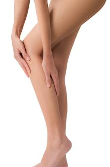 Vrouw die haar die been met het masseren van kalf en knie op pijngebieden houden op wit worden geïsoleerd