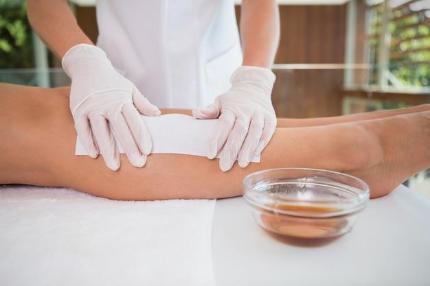 Vrouw die haar die benen krijgen door schoonheidstherapeut worden waxed