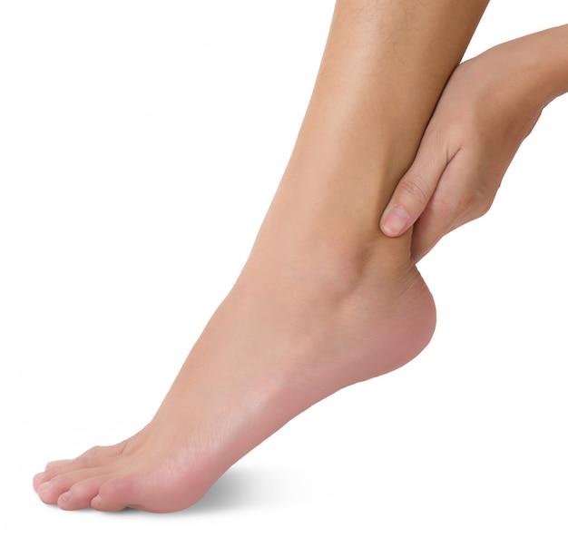 Vrouw die haar die voet houdt en enkel op pijngebied masseert op wit wordt geïsoleerd