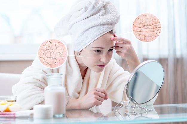 Vrouw die haar droge huid met barsten en met eerste rimpels bekijkt. cirkels verhogen de huid als een vergrootglas vergrootglas