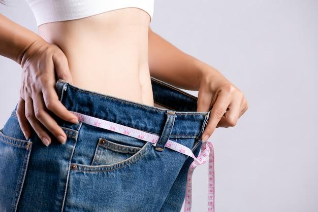 Vrouw die haar dunne taille met een meetlint meet. gezondheidszorg en dieet