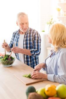 Vrouw die haar echtgenoot bekijkt die de salade in de keuken voorbereidt