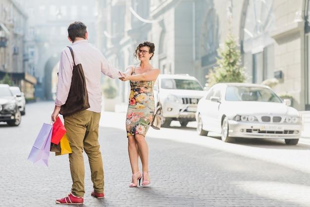 Vrouw die haar echtgenoot trekt terwijl het winkelen op straat