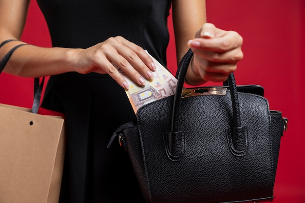 Vrouw die haar geld in haar beurs zet