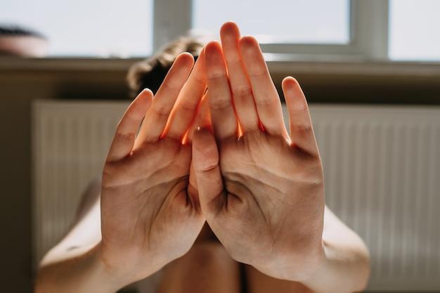 Vrouw die haar gezicht bedekt met haar handen