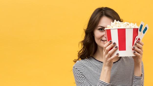 Vrouw die haar gezicht behandelt met 3d glazen en emmer met popcorn