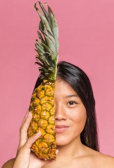 Vrouw die haar gezicht behandelt met ananas en camera bekijkt
