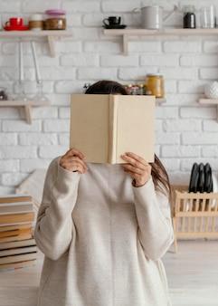Vrouw die haar gezicht behandelt met boek