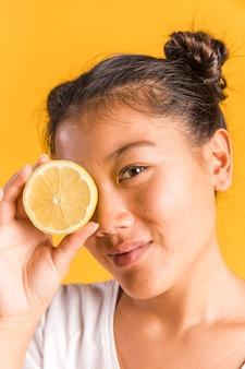 Vrouw die haar gezicht behandelt met citroen
