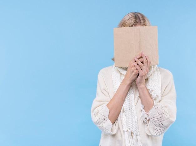 Vrouw die haar gezicht behandelt met een boek