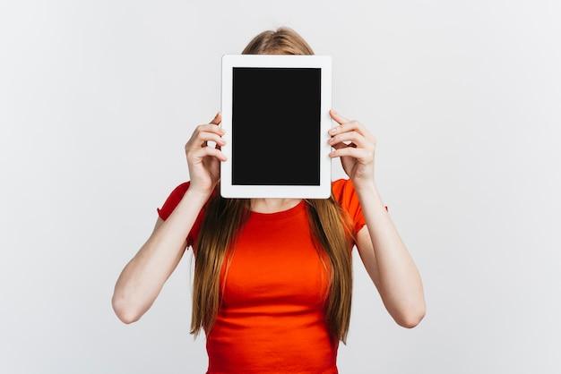 Vrouw die haar gezicht behandelt met een tabletmodel