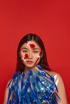 Vrouw die haar gezicht en lichaam bedekt met rood en blauw plastic vaatwerk met exemplaarruimte