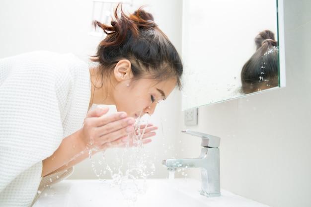 Vrouw die haar gezicht in de ochtend vóór douche reinigt