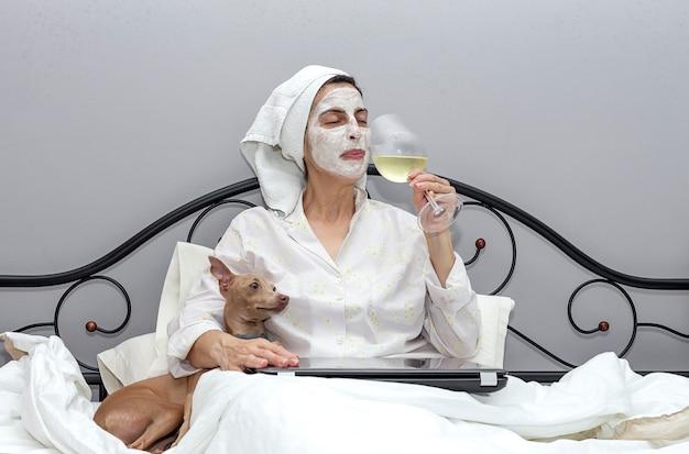 Vrouw die haar gezicht met een gezichtsmasker in bed, met hond behandelt, die een glas wijn drinkt