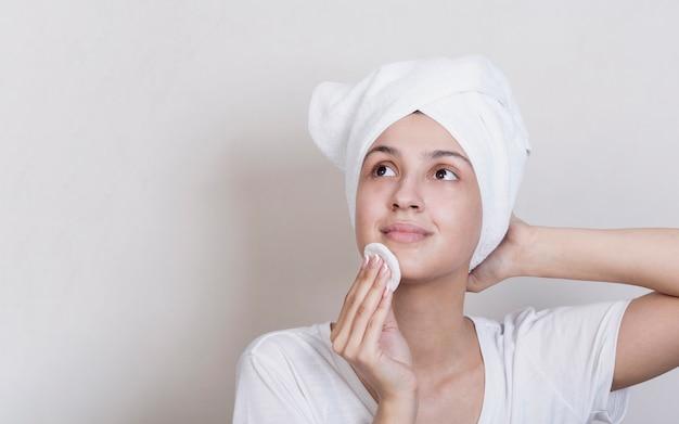 Vrouw die haar gezicht met exemplaarruimte schoonmaakt