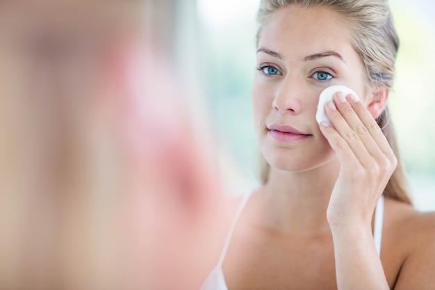 Vrouw die haar gezicht met katoenen stootkussen in de badkamers afveegt